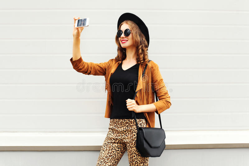 Fashion happy young smiling woman taking photo picture self-portrait on smartphone wearing retro elegant hat, sunglasses. Brown jacket and black handbag over stock photos