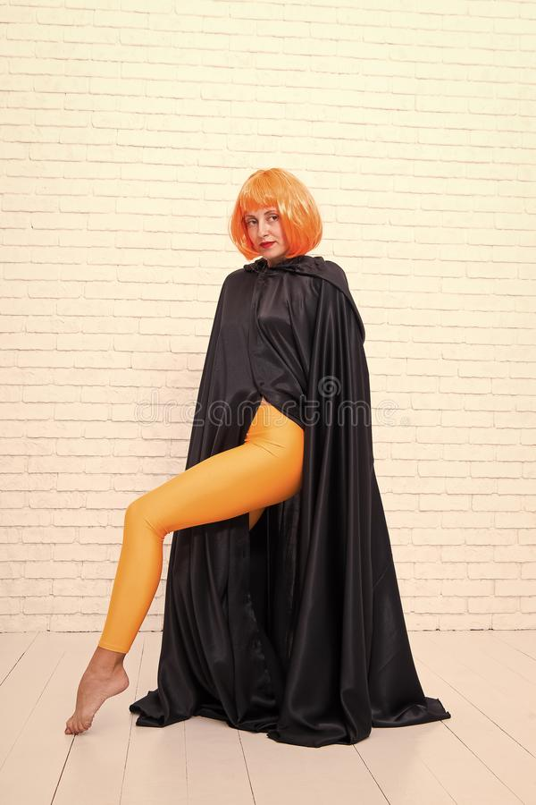 Fashion is her life. Fashion model wearing orange wig hair and black robe on white brickwall. Sexy girl with fashion stock photography