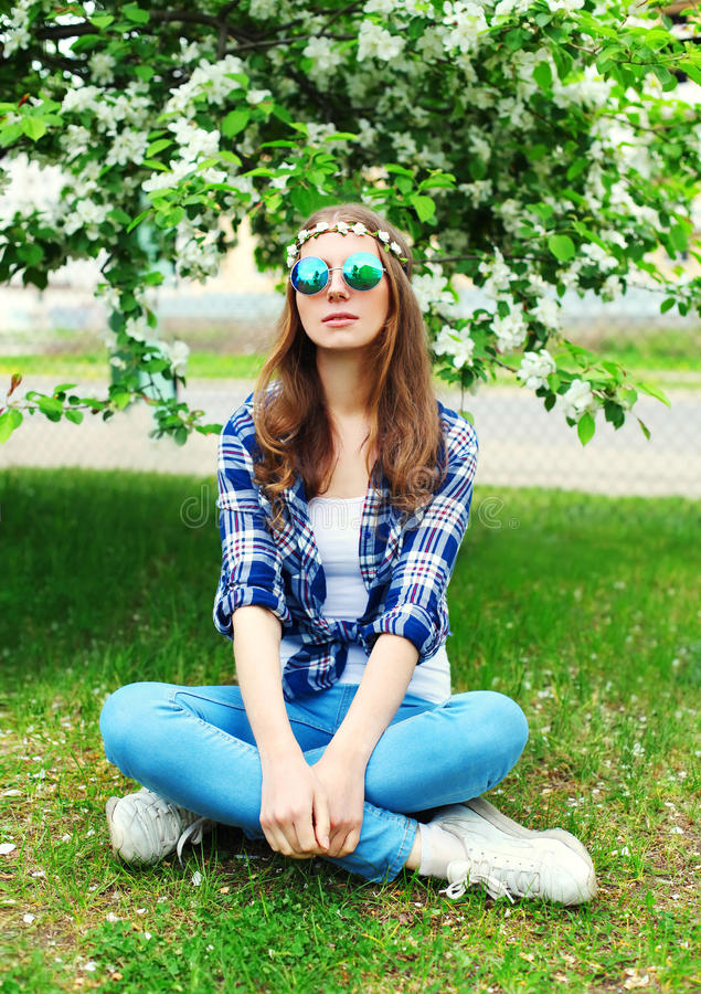 Fashion hippie woman sitting resting on grass in flowering garden royalty free stock image