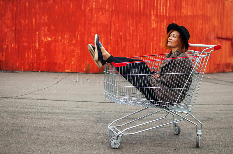 Fashion hipster cool girl in shopping cart having fun against th stock image