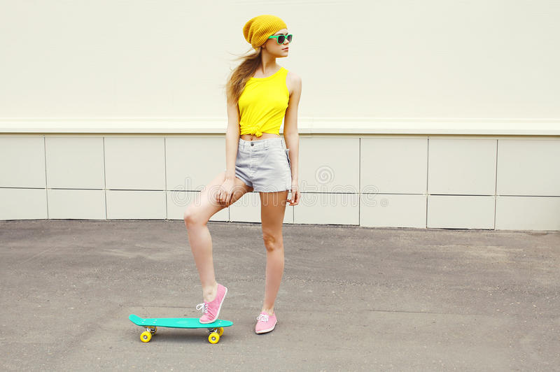 Fashion hipster cool woman with skateboard stock photo