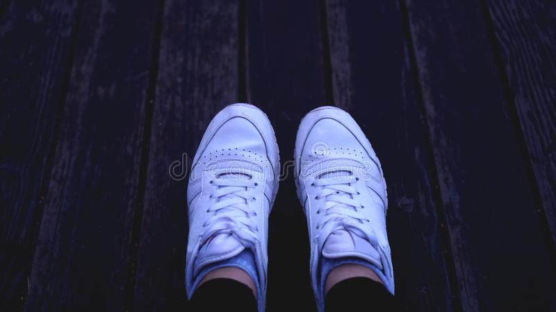 Fashion hipster cool woman with white sneakers, vintage toned colors royalty free stock photography