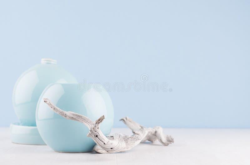 Fashion home decor in modern elegant japanese style - light soft blue ceramic vases and old shabby branch on white wood background stock images