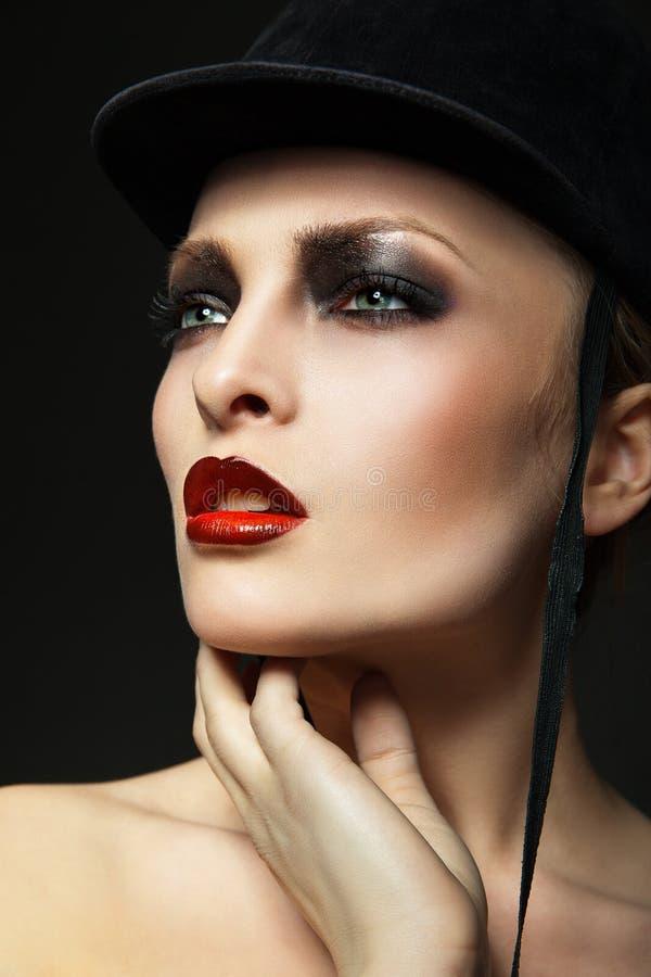 Fashion horsewoman wearing black hat. Blond fashion horsewoman wearing hat posing over black background royalty free stock photos
