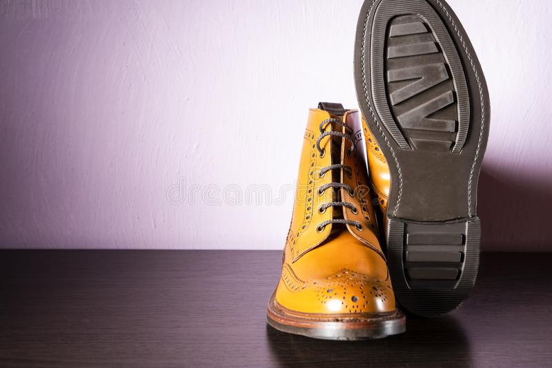 Fashion Ideas. Pair Male Tanned Leather Brogued Boots With One Shoe Turned Over. On Wooden Background. Fashion Ideas. Male Tanned Leather Brogued Boots With One royalty free stock images