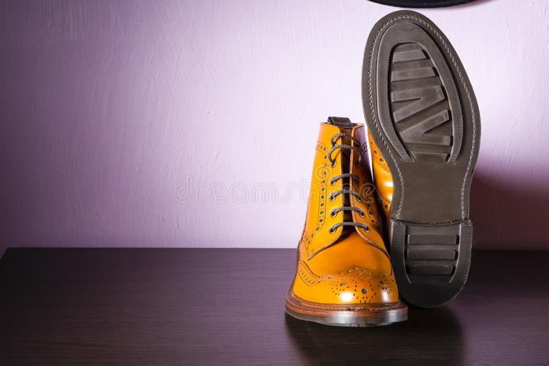 Fashion Ideas. Pair Male Tanned Leather Broggued Boots With One Shoe Turned Over. Fashion Ideas. Pair Male Tanned Leather Brogued Boots With One Shoe Turned royalty free stock photography