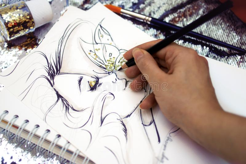 Fashion illustrator drawing a sketch with glitter.  stock image
