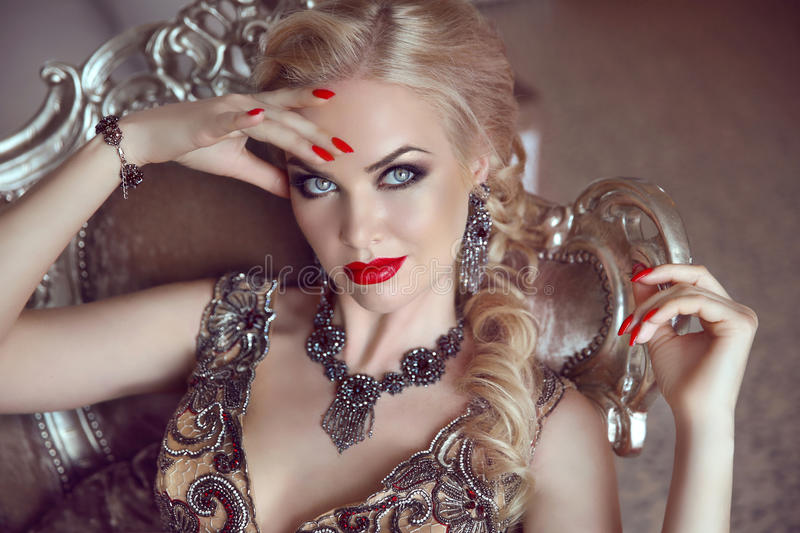 Fashion indoor portrait of beautiful sensual blond woman with ma. Keup in luxurious dress with bijou, posing on modern armchair with sliver frames royalty free stock image