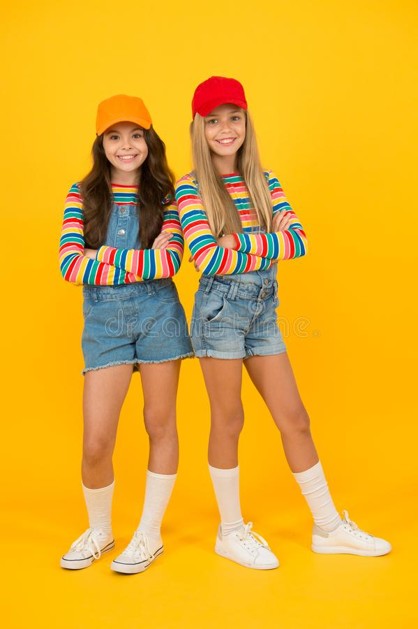 Fashion inspired by the sneaker culture. Happy kids keeping arms crossed with fashion look. Fashion small girls in stock images