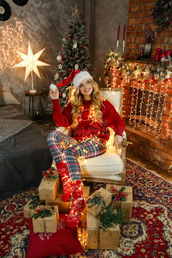 Beautiful girl with blond hair in elegant dress posing in decorated room with Christmas tree and presents royalty free stock images