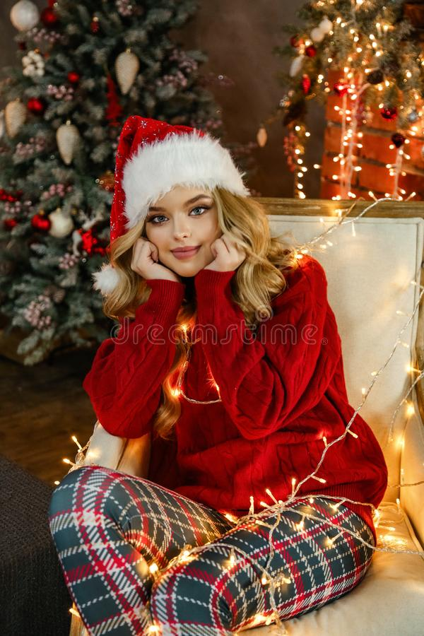 Beautiful girl with blond hair in elegant dress posing in decorated room with Christmas tree and presents royalty free stock photo
