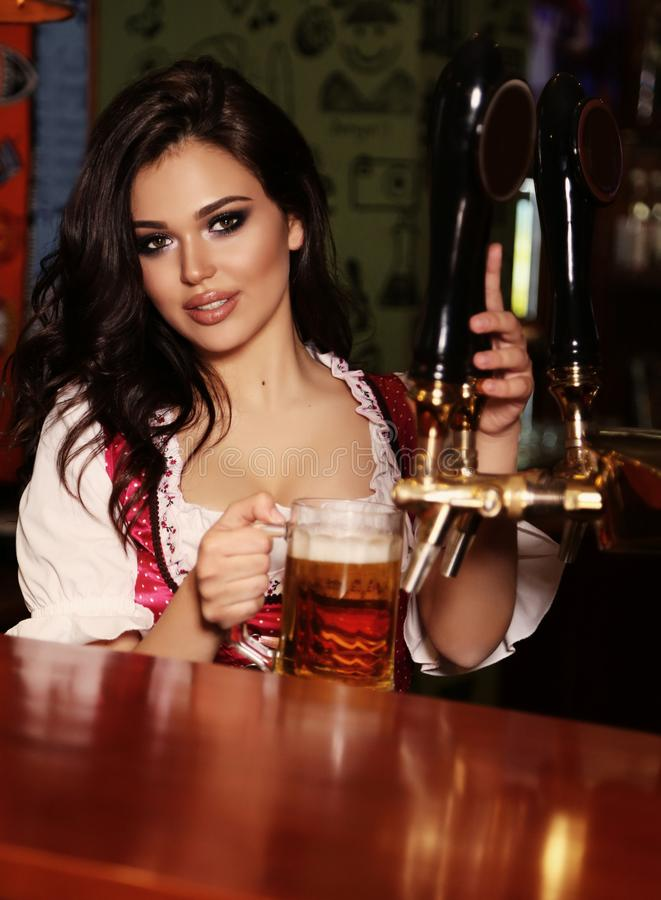 Beautiful woman bartender posing in bar counter with beer. Fashion interior photo of beautiful woman bartender posing in bar counter with glass of beer stock photo