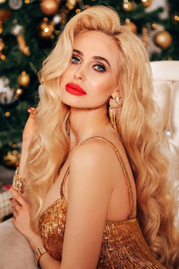 Beautiful woman with long blond hair in elegant dress posing near decorated Christmas tree stock images