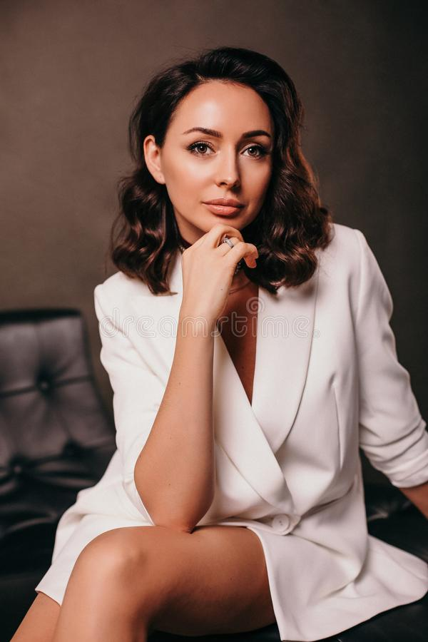 Businesslike woman with dark hair in elegant office clothes. Fashion interior photo of businesslike woman with dark hair in elegant office clothes stock image