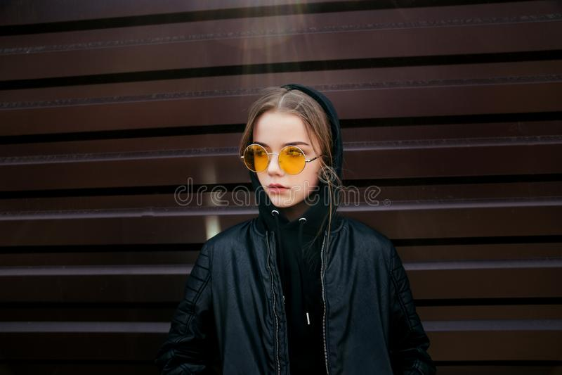 Fashion kid concept - stylish girl child wearing black casual clothes and sunglasses posing summer in the city stock photo