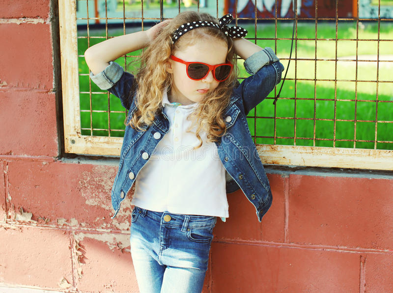 Fashion kid concept - stylish little girl child wearing a jeans royalty free stock image