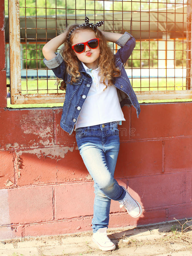 Fashion kid concept - stylish little girl child wearing a jeans. Clothes and sunglasses posing summer in the city royalty free stock photography