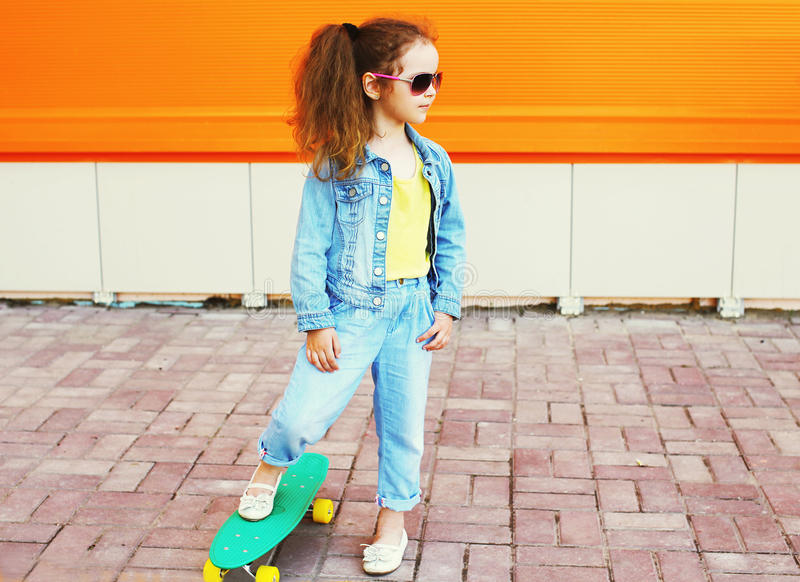 Fashion kid concept - stylish little girl child wearing a jeans. Clothes and sunglasses with skateboard in city enjoys summer against the colorful orange wall royalty free stock photo