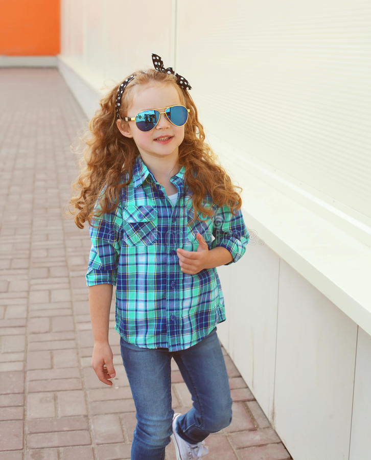 Fashion kid concept - stylish little girl child wearing a shirt. And sunglasses posing outdoors in the city royalty free stock photos