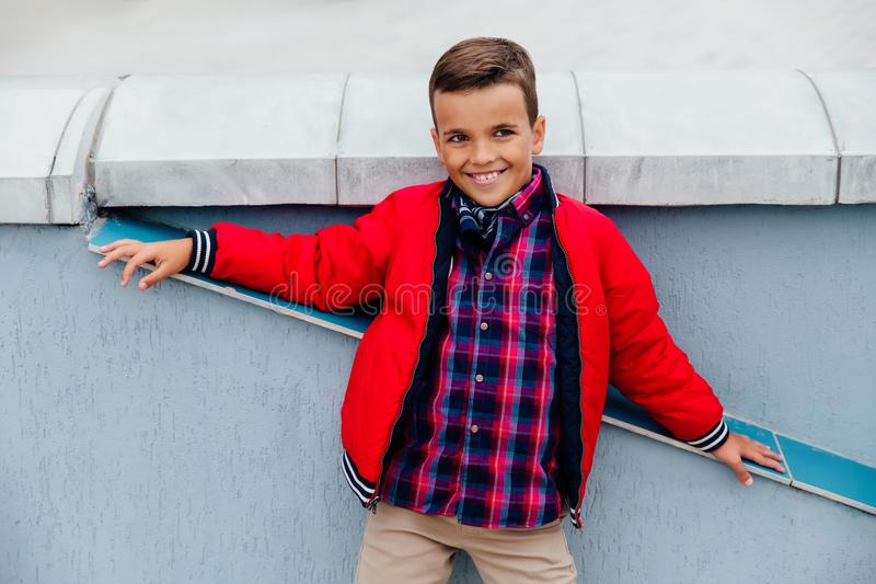 Fashion kid fall time in the city stands against the background of a concrete wall. The model is dressed in a red jacket, checkered shirt. Posing smiles royalty free stock image