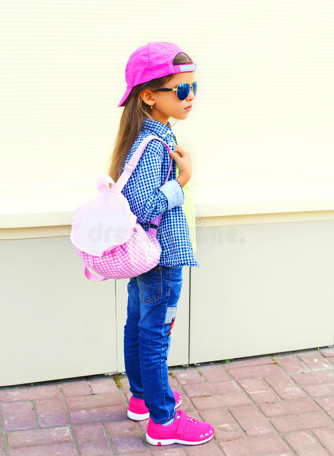 Fashion kid little girl wearing a baseball cap and backpack royalty free stock photo
