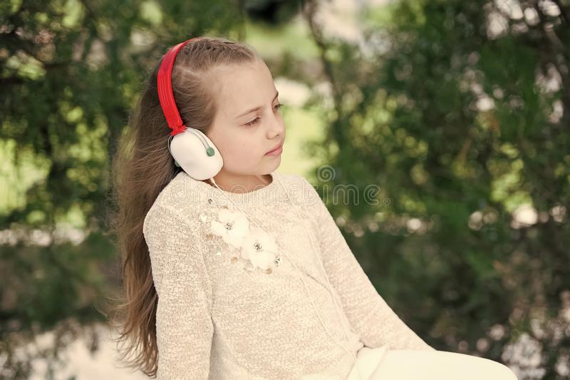 Fashion kid and modern technology. Melody sound and mp3. Little girl listen music in summer park. Child enjoy music in. Headphones outdoor. Summer vacation rest royalty free stock image
