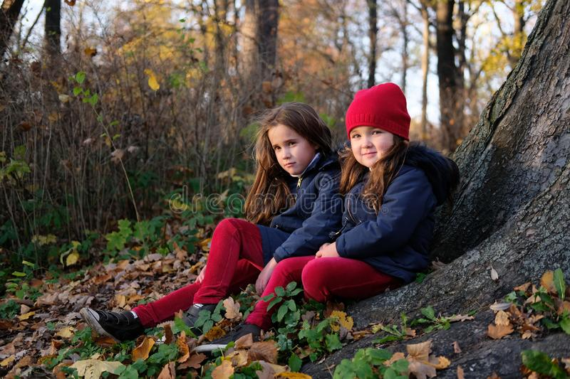 Fashion kids in autumn park. Close up lifestyle portrait of two beautiful caucasian girls outdoors, wearing cute trendy outfit in stock photography