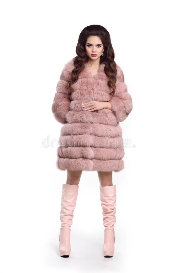 Fashion lady in pink fur coat and leather high boots, beautiful royalty free stock photo