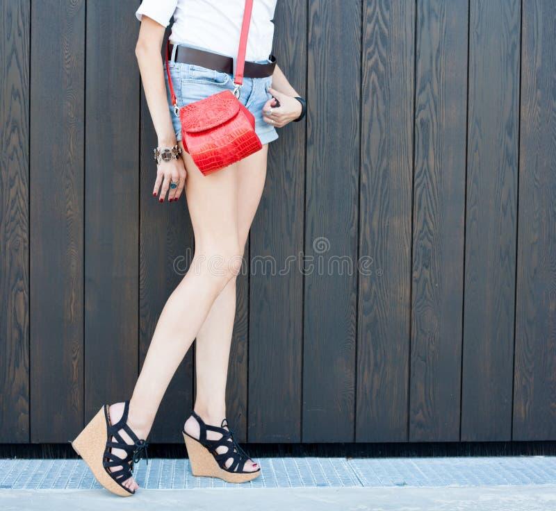 Fashion leggy girl in a beautiful high-heeled shoes in short denim shorts summer posing near the dark wall. Close-up. Super fashion leggy girl in a beautiful royalty free stock photo