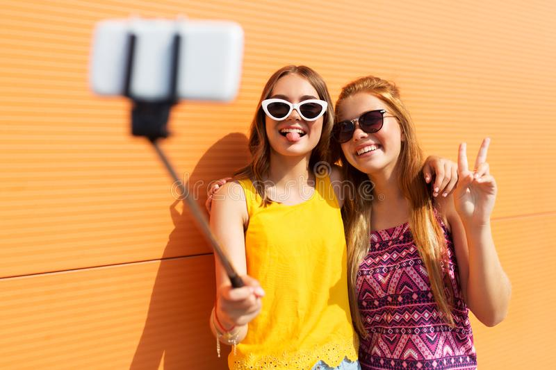 Teenage girls taking picture by selfie stick. Fashion, leisure and people concept - smiling teenage girls taking picture by smartphone on selfie stick and stock image