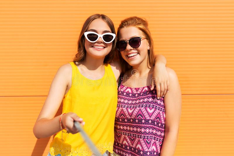 Teenage girls taking selfie outdoors in summer. Fashion, leisure and people concept - smiling teenage girls taking selfie by monopod outdoors in summer royalty free stock image