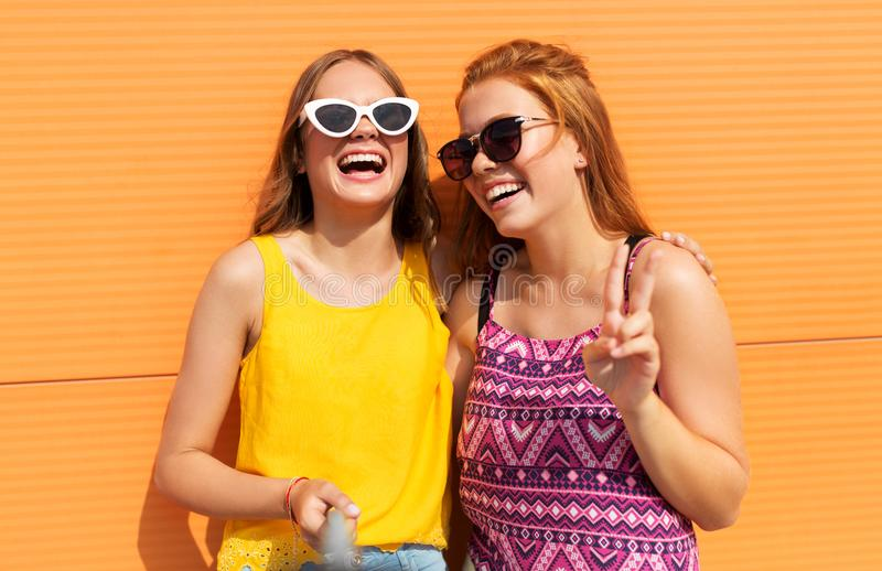 Teenage girls taking selfie in summer. Fashion, leisure and people concept - smiling teenage girls taking selfie by monopod and showing peace outdoors in summer royalty free stock photo