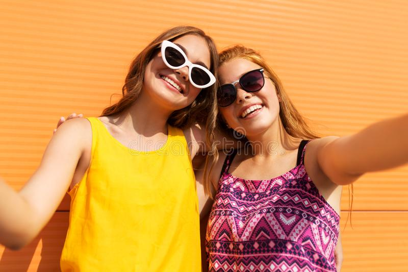 Teenage girls taking selfie outdoors in summer. Fashion, leisure and people concept - smiling teenage girls taking selfie outdoors in summer stock images