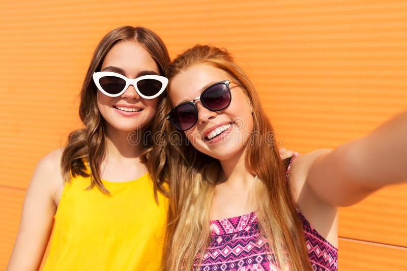 Teenage girls taking selfie outdoors in summer. Fashion, leisure and people concept - smiling teenage girls taking selfie outdoors in summer stock photo