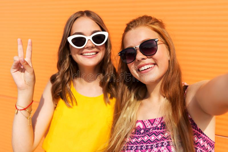Teenage girls taking selfie in summer. Fashion, leisure and people concept - smiling teenage girls taking selfie and showing peace outdoors in summer stock photo