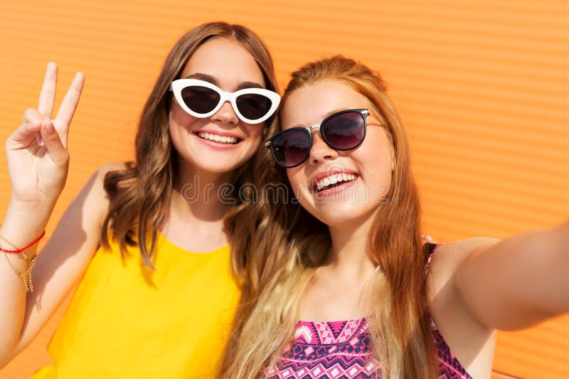 Teenage girls taking selfie in summer. Fashion, leisure and people concept - smiling teenage girls taking selfie and showing peace outdoors in summer stock image