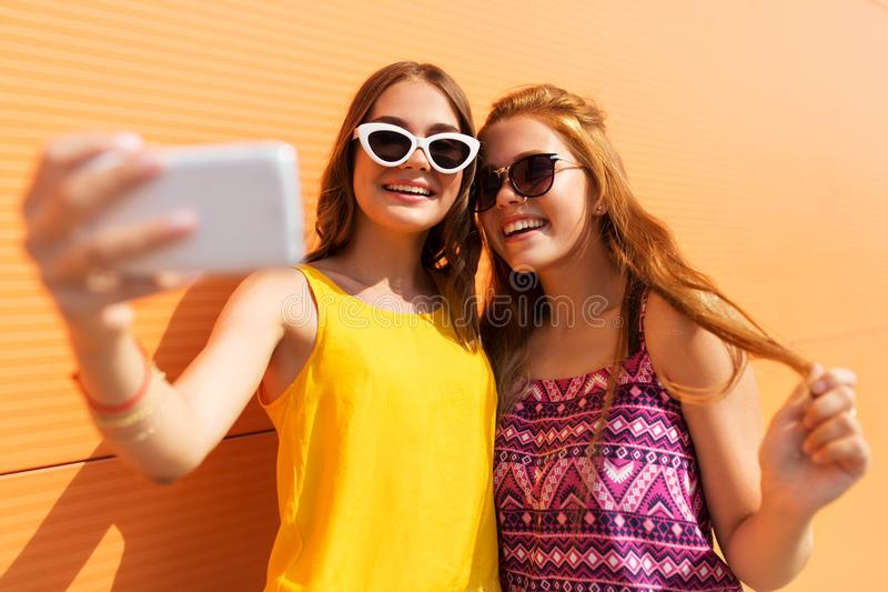 Teen girls taking selfie by smartphone in summer. Fashion, leisure and technology concept - smiling teenage girls taking selfie by smartphone outdoors in summer royalty free stock photography