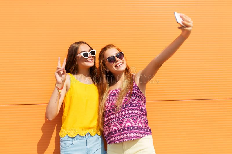 Teen girls taking selfie by smartphone in summer. Fashion, leisure and technology concept - smiling teenage girls taking selfie by smartphone and showing peace royalty free stock images