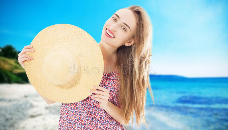 Fashion and lifestyle concept - beautiful woman in hat enjoying summer vacation in the beach sea islands background. Girl hold stock images