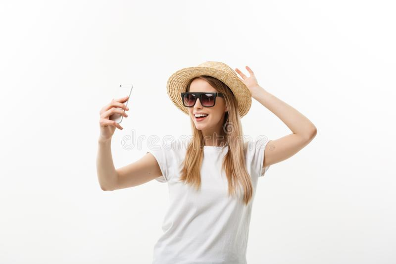Fashion and Lifestyle Concept: pretty young woman wearing a hat, sunglasses takeing a photo of herself by mobile phone royalty free stock photo
