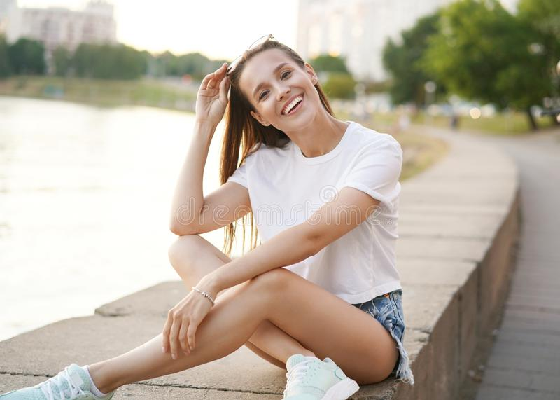 Fashion lifestyle portrait pretty woman posing in the city summer, evening sunset sunny light. royalty free stock images