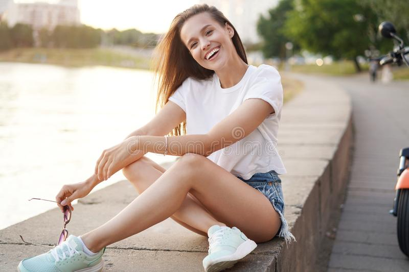 Fashion lifestyle portrait pretty woman posing in the city summer, evening sunset sunny light. royalty free stock photos