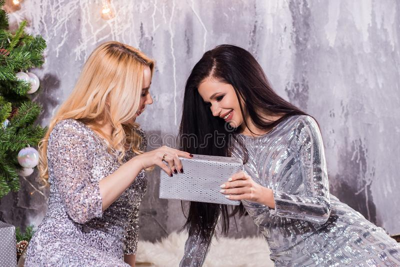 Fashion lifestyle portrait of two girls friends holding birthday bright presents, wearing trendy clothes and sparkled tinsel. Going crazy, and making funny stock photo