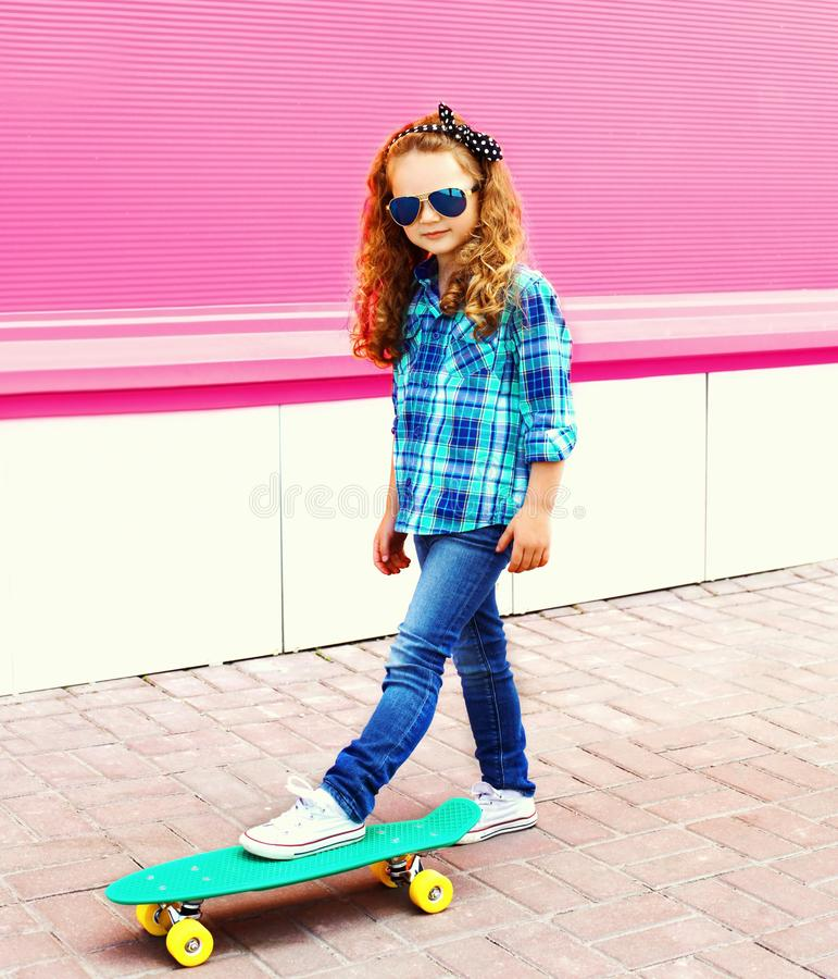 Fashion little girl child in checkered shirt with skateboard in city on colorful pink royalty free stock photos