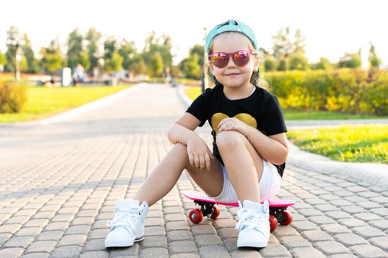 Fashion little girl child sitting on skateboard in city, wearing a sunglasses and t-shirt. stock images