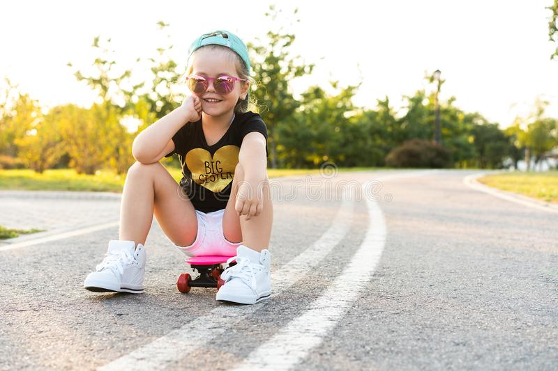 Fashion little girl child sitting on skateboard in city, wearing a sunglasses and t-shirt. royalty free stock photos