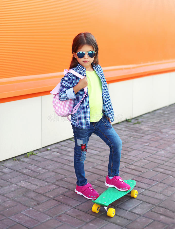 Fashion little girl child with skateboard wearing a sunglasses and checkered shirt and backpack over orange stock photos