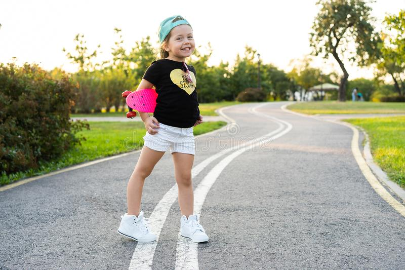 Fashion little girl child with skateboard wearing a sunglasses and hipster shirt. Fashion little girl child with skateboard wearing a sunglasses and t-shirt stock photo