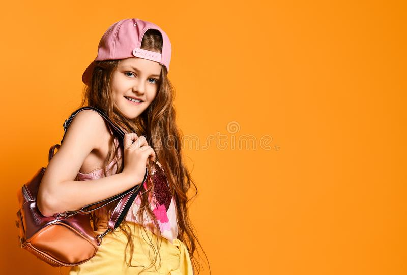 Fashion little girl child wearing pink baseball cap, backpack on a yellow studio wall. royalty free stock image
