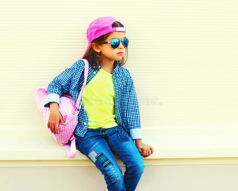 Fashion little girl child wearing sunglasses, baseball cap, backpack on city street on white stock photos